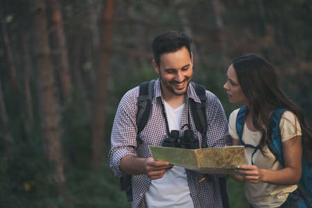 Young couple is hiking in forest. They are looking at map.