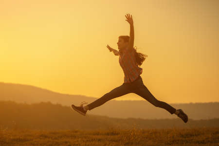 Happy child jumping in nature in sunset.