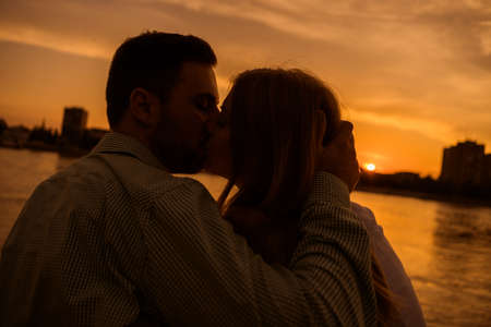 Happy couple is kissing in sunset in the city.