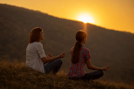 Happy grandmother and granddaughter meditating in sunset.