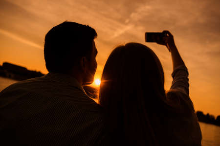 Happy couple is taking selfie in sunset in the city.