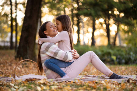 Daughter is kissing her mother in autumn in park. Фото со стока