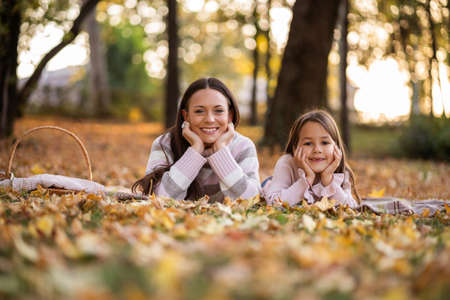 Mother and daughter enjoying autumn in park.