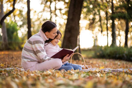 Mother and daughter enjoying autumn in park. Little girl is learning to read. Фото со стока