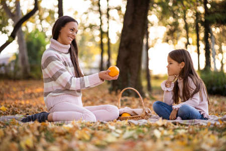 Mother and daughter having picnic in park in autumn.