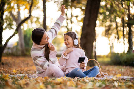 Mother and daughter enjoyng autumn in park. They are listening music on headphones.