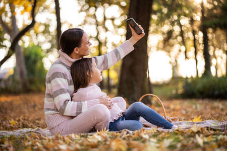 Mother and daughter using smartphone in autumn in park.