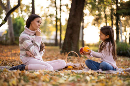 Mother and daughter having picnic in park in autumn