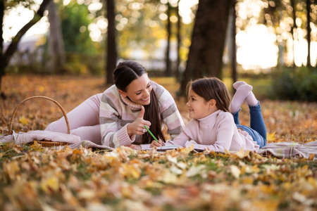 Mother and daughter enjoying autumn in park. Little girl is drawing.
