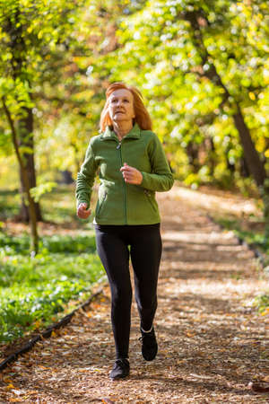 Senior woman is jogging in park. Healthy lifestyle.