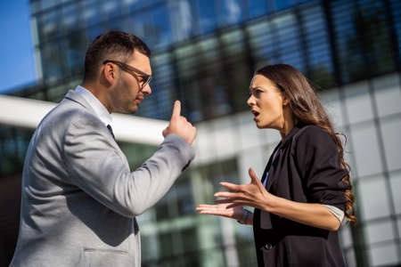 Business colleagues are arguing outside the company building.