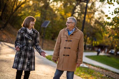 Happy senior couple is walking in park in autumn. Фото со стока