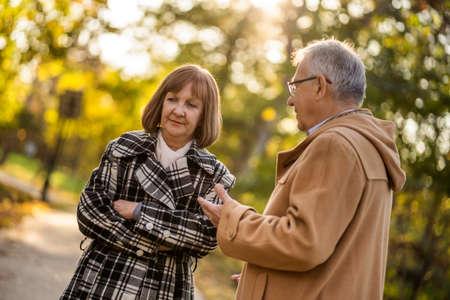 Senior couple is talking in park in autumn.