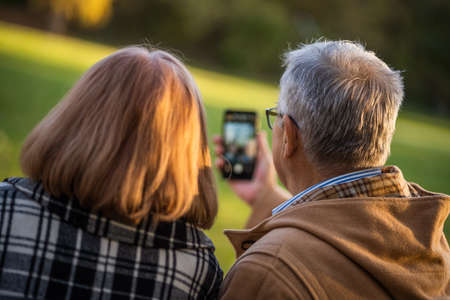 Senior couple is taking selfie in park with smartphone.