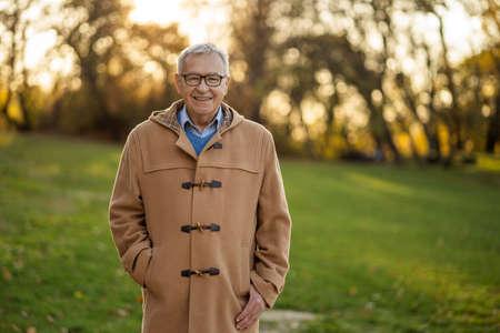 Portrait of happy senior man in park in autumn.