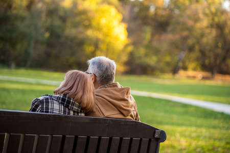 Romantic senior couple is sitting on bench in park and enjoying autumn.