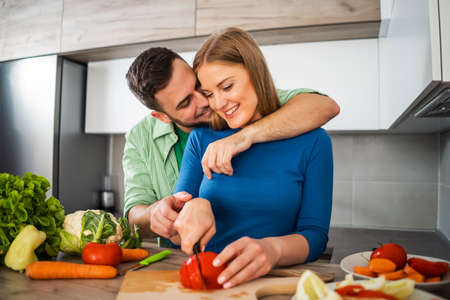 Young couple is preparing meal in their kitchen. Фото со стока