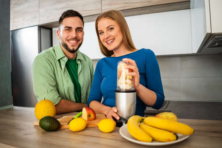 Young couple is preparing juice in their kitchen.