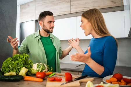 Young couple is arguing in their kitchen.