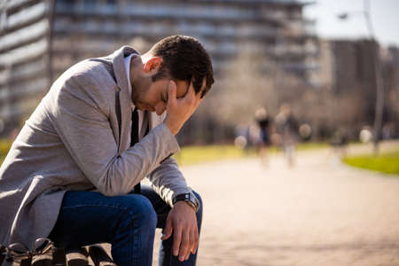 Young businessman is sitting in park after being fired. He is depressed.