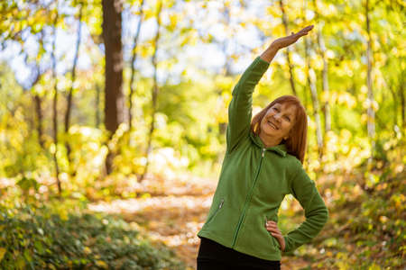 Senior woman is exercising in park on sunny day.