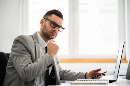 Young pensive businessman is working in office. Фото со стока