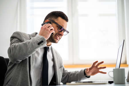 Furious businessman is talking on phone.