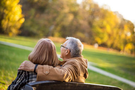 Romantic senior couple is sitting on bench in park and enjoying autumn. Фото со стока