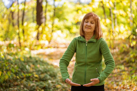 Senior woman is practicing Tai Chi exercise in park. Stock Photo