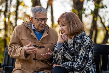 Senior couple is sitting on bench in park and talking.