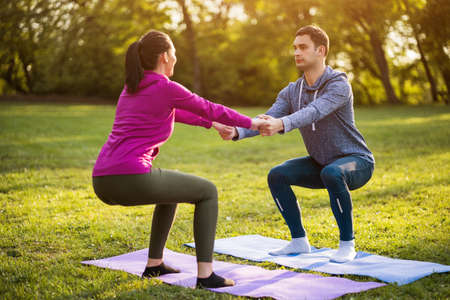 Couple is exercising in park. Exercise for sciatica recovery.