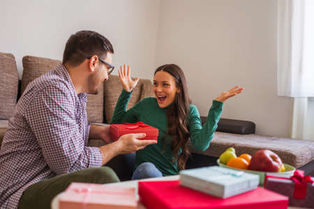 Happy couple is sharing gifts in their home.