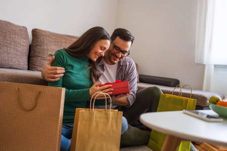 Happy couple is sharing gifts in their home. Stock Photo - 136664074