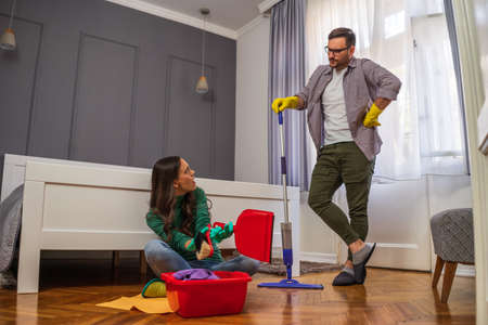 Woman is lazy. Man is telling her to continue cleaning their apartment. Stock Photo