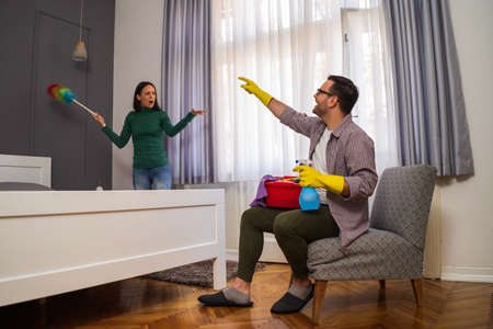 Woman is angry because her husband is lazy and avoids cleaning apartment. Фото со стока