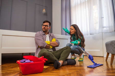 Man is lazy. His wife is telling him to continue cleaning their apartment. Stock Photo