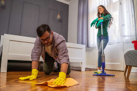 Young couple is cleaning their apartment. Man is bored. Фото со стока