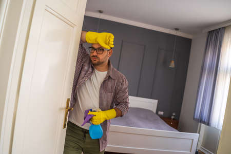 Young man is obsessively cleaning the apartment. He is tired. Фото со стока