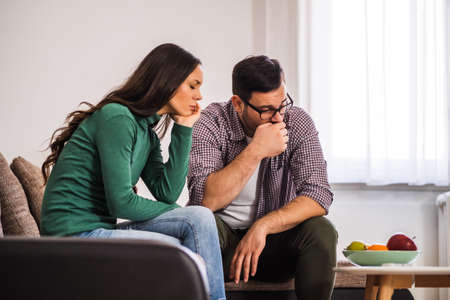 Man and woman are sitting at sofa and not talking to each other. Relationship problems. Фото со стока