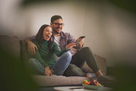 Happy couple in love is relaxing at home. They are watching tv.