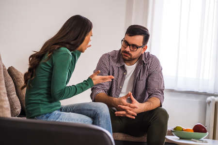 Man and woman are sitting at sofa and arguing. Relationship problems. Фото со стока