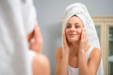 Portrait of young happy woman who is satisfied with her skin.