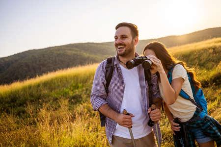 Feliz pareja está de excursión en la montaña. Observan la naturaleza con binoculares.