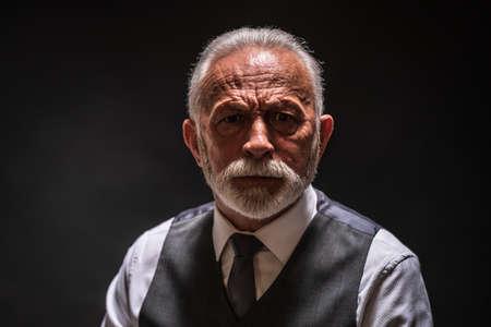 Portrait of serious senior man on black background.