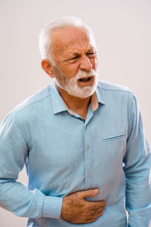 Portrait of senior man who is having pain in stomach.