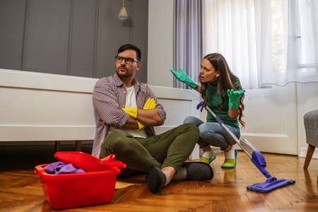 Couple is cleaning their apartment. They are arguing.