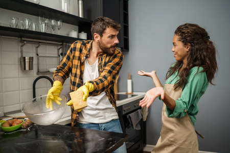 Young multiethnic couple is cleaning their kitchen. Woman is lazy and man is angry.