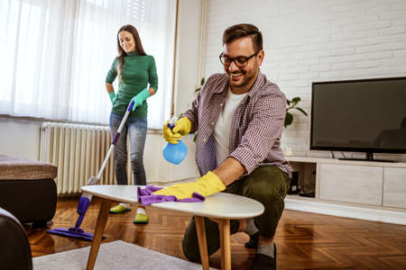 Young happy couple is cleaning their apartment. Stock Photo