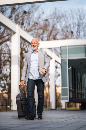 Happy senior businessman is arriving from business trip.