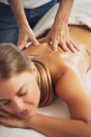 Professional masseur doing therapeutic massage. Woman enjoying massage in her home. Young woman getting relaxing body massage. Reklamní fotografie